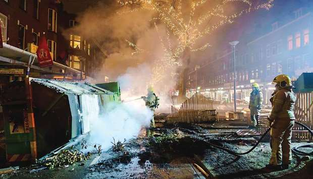 Firefighters work to extinguish a fire on the Groene Hilledijk in Rotterdam, late on Monday, after a