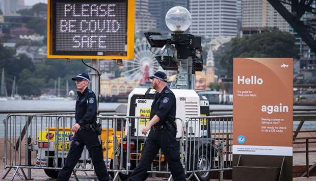 New South Wales police officers walk past signs on display in front of the Opera House as Covid-19 r