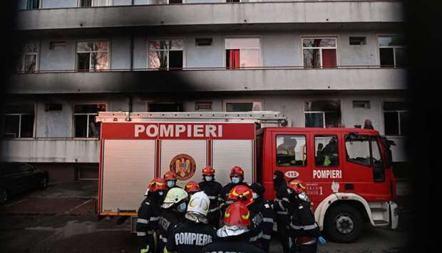 Firemen gather in the courtyard of the Matei Bals infectious diseases hospital's burned pavilion in
