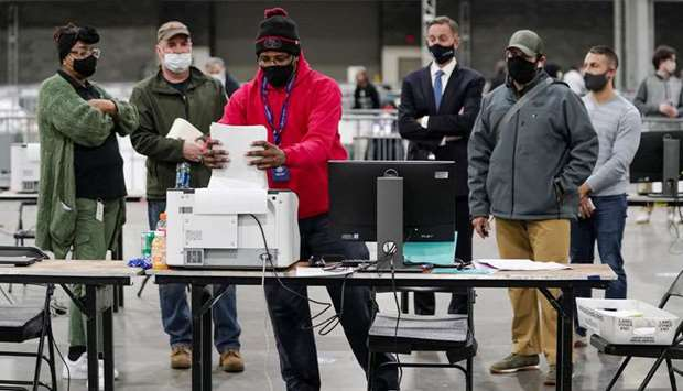 A Fulton County election worker puts absentee ballots in a scanner as election observers look on, at