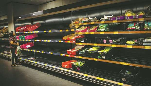 A lone shopper surveys cleared out shelves in the wake of panic buying in Brisbane yesterday.