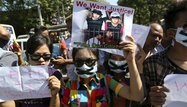 Protesters hold pictures of Zaw Lin and Win Zaw Htun, two Myanmar migrant workers in Thailand