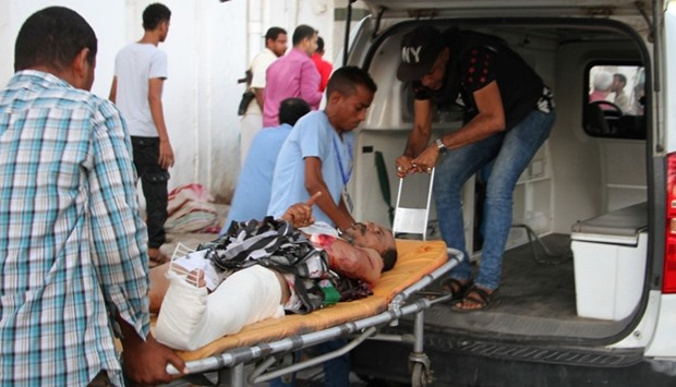 A wounded Yemeni man is taken off an ambulance after a suicide bomber killed 35 soldiers and wounded