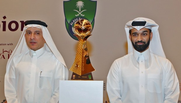 CEO of Qatar Airways, Akbar al-Baker (L), and Secretary General of the Qatar 2022 Supreme Committee, Hassan al-Thawadi, pose with the cup of the match during a press conference in Doha