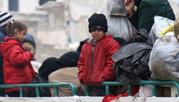 A child reacts while waiting with others to be evacuated from a rebel-held sector of eastern Aleppo,