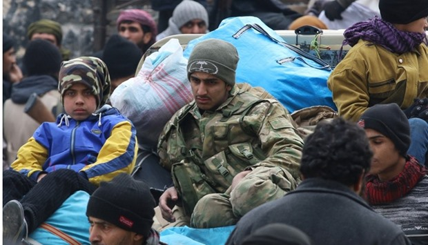 Rebel fighters and civilians gather as they wait to be evacuated from a rebel-held sector of eastern