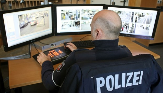 A policeman watches monitors displaying images delivered by surveillance cameras in Marxloh