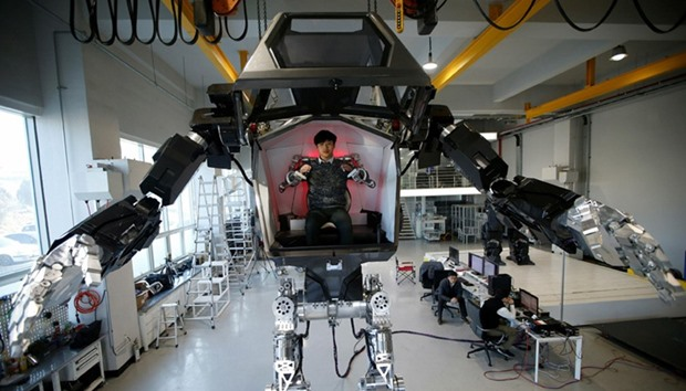 "An employee controls the arms of a manned biped walking robot ""METHOD-2"" during a demonstration"