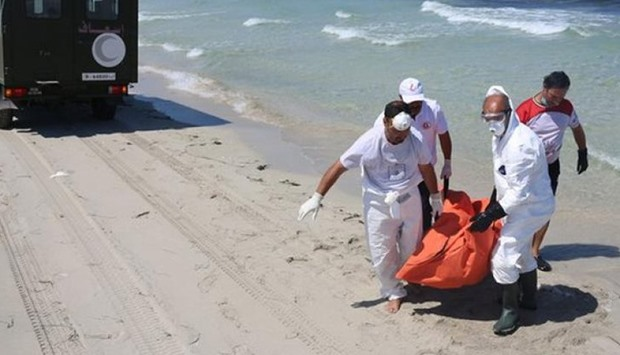 Workers carry a body that was washed up on shore