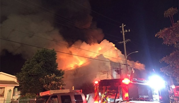 Flames rise from the top of a warehouse, which caught fire during a dance party in Oakland