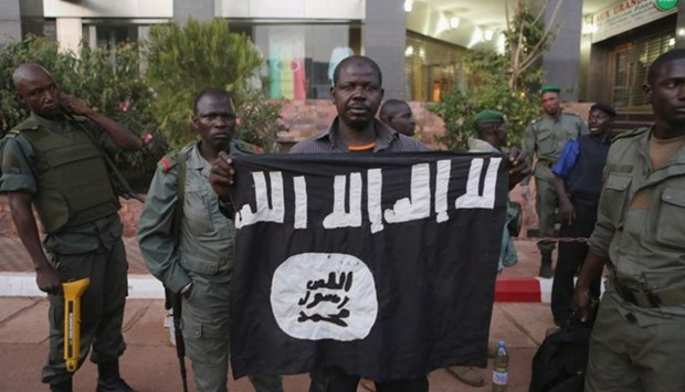 Malian security officials display the flag of a militant group