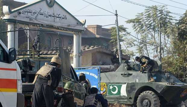 Pakistani security personnel take position outside an Agriculture Training Institute after an attack