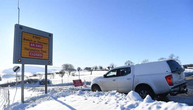 A sign alerts drivers to road closures near Wrexham, north Wales as heavy snowfall blankets the area