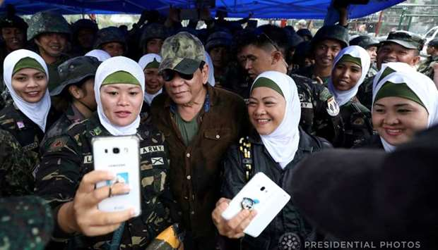 Philippine President Rodrigo Duterte (C) poses for a picture with female soldiers during his visit a