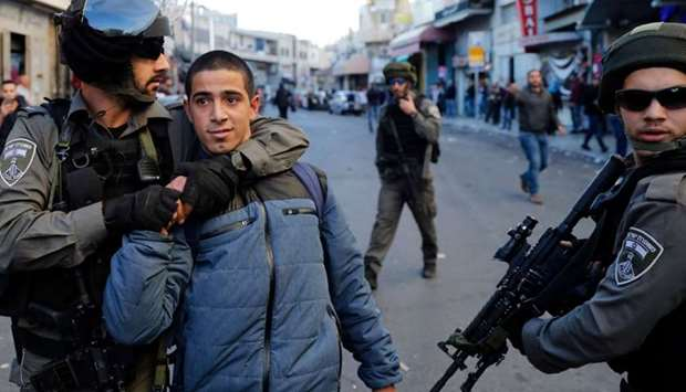 A Palestinian man is detained by Israeli security forces in Jerusalem on December 16, 2017, as demon