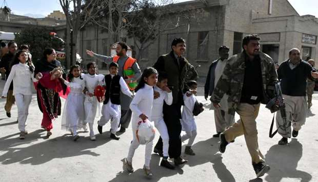 Policemen guide people after gunmen attacked the Bethel Memorial Methodist Church in Quetta, Pakista