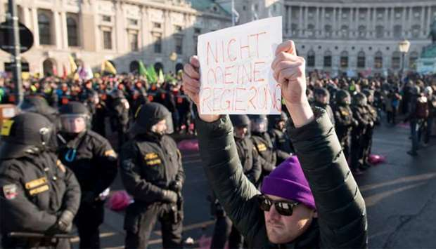 "A protester stands in front of the riot policemen and holds a sign reading ""Not my Government"" durin"