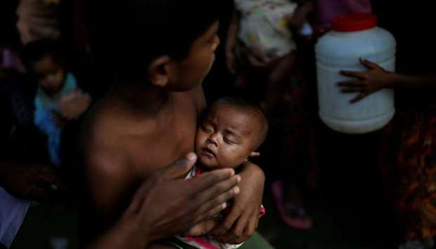 A boy holds a baby as Rohingya refugees wait to receive food supplies at a World Food Programme (WFP