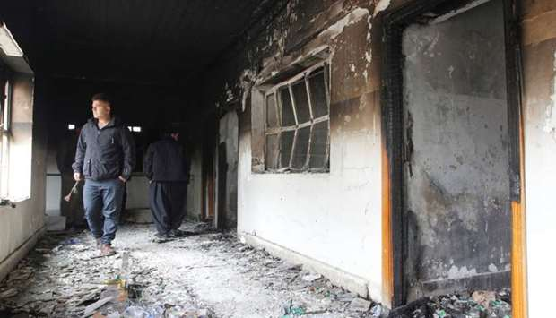 Men are seen at the Patriotic Union of Kurdistan (PUK) building after it was set on fire by Kurdish