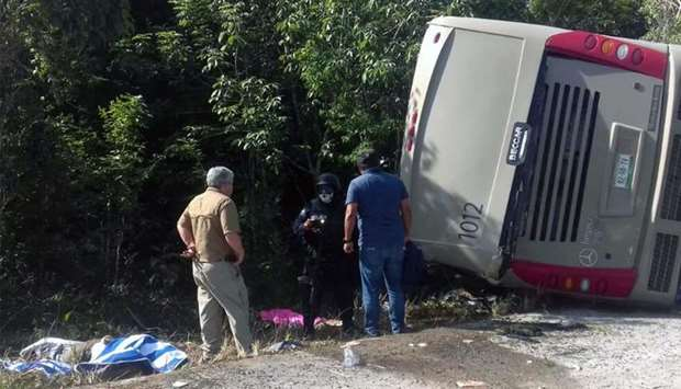 Mexican police officers and paramedics work in the scene of a road accident in Quintana Roo state