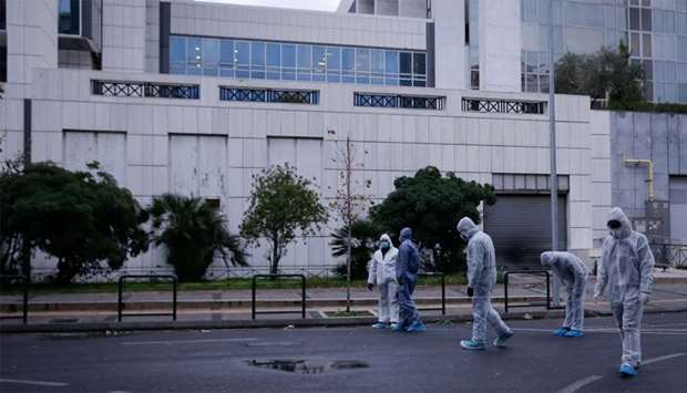 Police officers search for evidence after a bomb blast at a court building in Athens