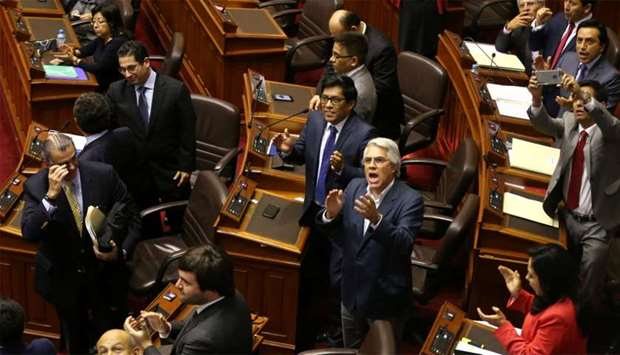 Lawmakers supporting Peru's President Kuczynski celebrate after he defeated an opposition bid to for