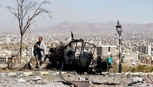 A Yemeni man takes a picture of the debris following an airstrike by the Saudi-led coalition