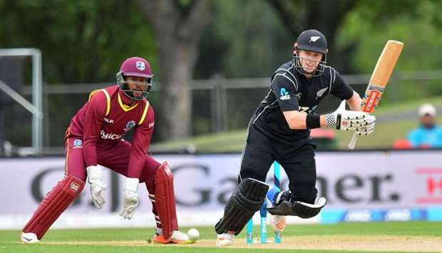 New Zealand's Henry Nicholls (R) bats as West Indies wicketkeeper Shai Hope (L) looks on