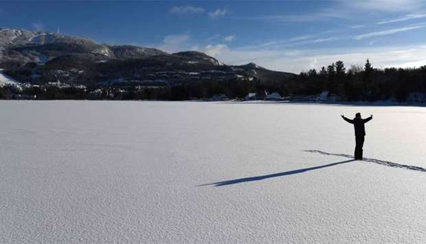 A man poses for a photo on frozen Lake Tremblant in the Laurentides region of Quebec, Canada