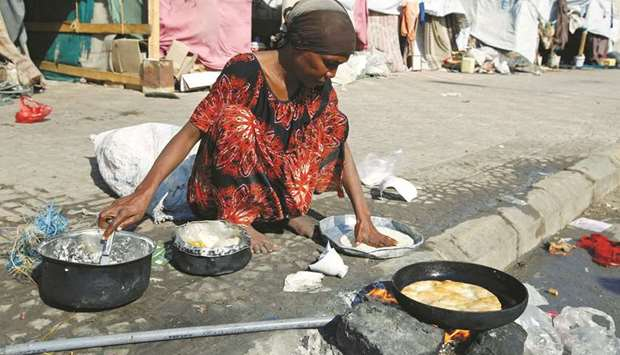 A woman displaced by the war in the northwestern areas of Yemen cooks outside her makeshift hut on a