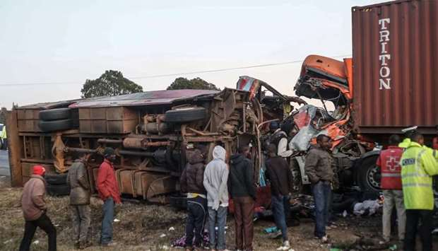 People look at the wreckage of a bus and a lorry that crashed in a head-on collision, killing thirty