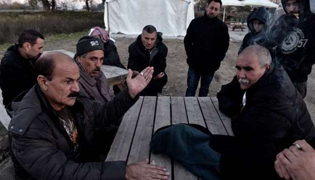 Yazidi refugees have a discussion as they sit outside at the Serres refugee camp, northern Greece, o
