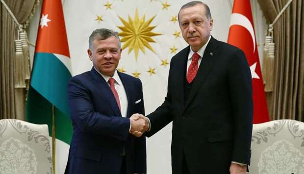 Turkish President Recep Tayyip Erdogan (R) shaking hands with King Abdullah II of Jordan during a me