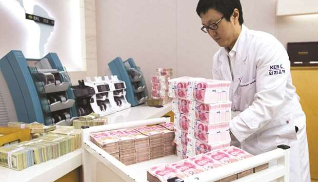 An employee arranges yuan banknotes at the Korea Exchange Bank headquarters in Seoul. China's moves