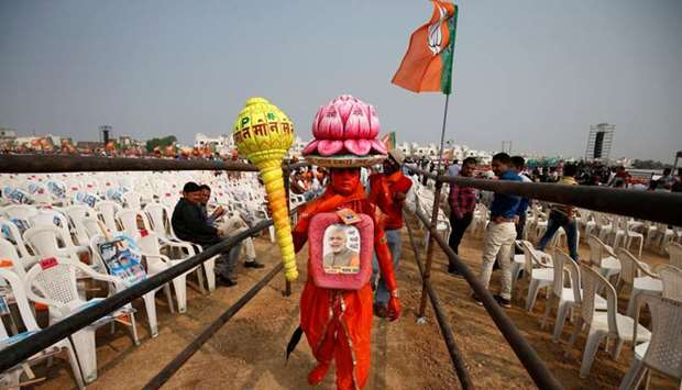 A supporter carries overhead a model of lotus, the election symbol of India's ruling Bharatiya Janat