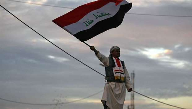 Iraqi man waves his national flag in Baghdad's Tahrir Square