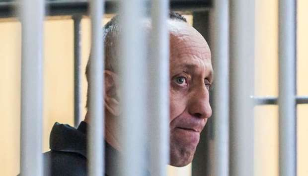 Mikhail Popkov stands inside a defendants' cage during a court hearing in Irkutsk
