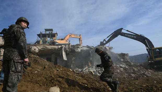 A South Korean soldier stands guard as construction equipment destroys a guard post in the Demilitar