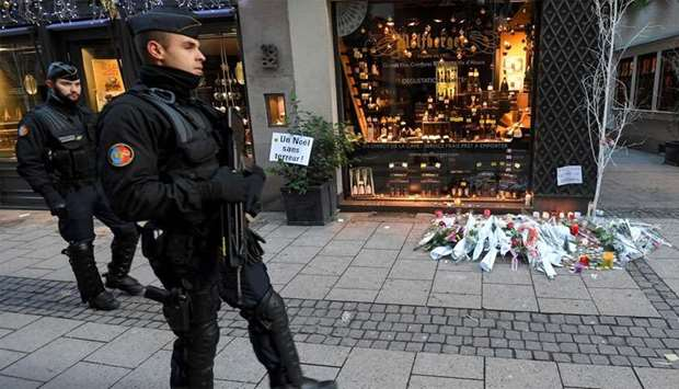 French gendarmes walk past flowers and candles laid in the street in tribute to the victims of a dea
