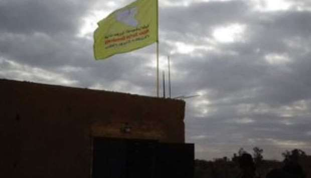 flag of  Syrian Democratic Forces flying atop a building in Hajin.