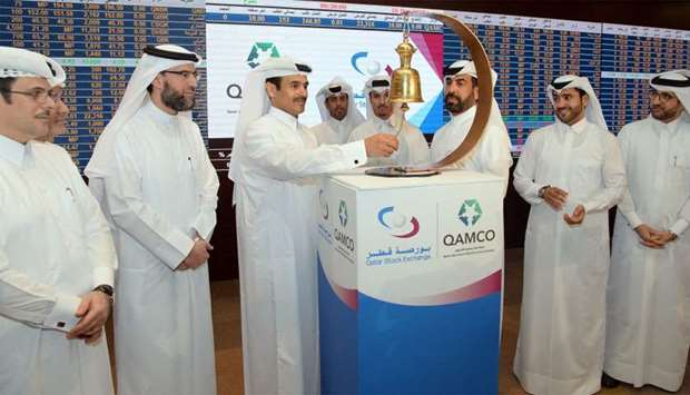 HE al-Kaabi rings the customary bell to announce the advent of Qamco on the QSE; also seen are al-Ma