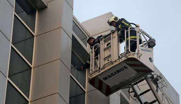 Firefighter breaks a glass window of a government hospital after it caught a fire in Mumbai