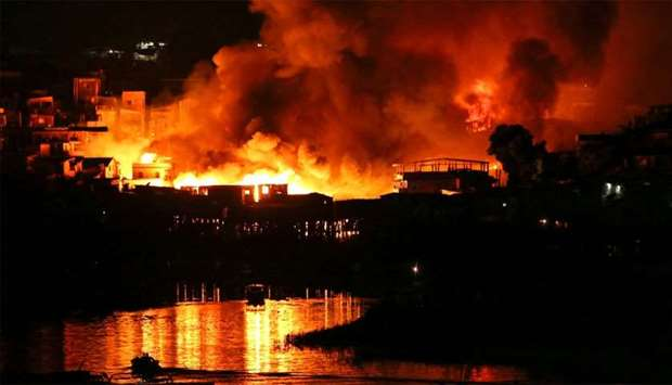 Houses on fire are seen at Educando neighbourhood, a branch of the Rio Negro, a tributary to the Ama