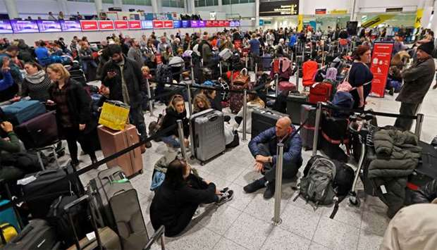 Passengers wait around in the South Terminal building at Gatwick Airport after drones flying illegal