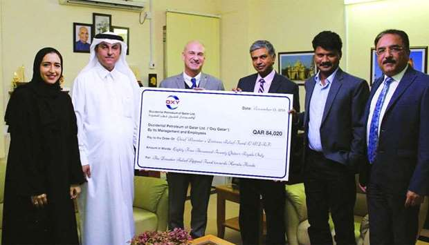 Oxy Qatar representatives hand over the cheque to the Indian ambassador P Kumaran