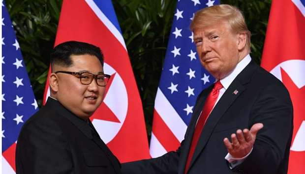 Trump (R) gestures as he meets with North Korea's leader Kim Jong Un (L) at the start of their histo