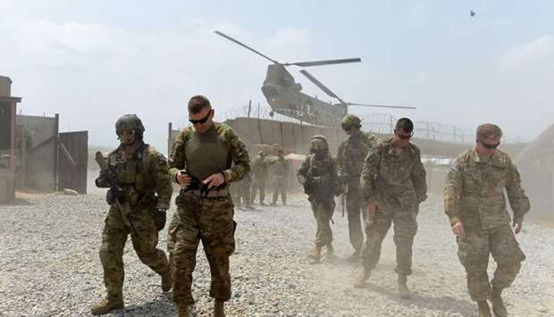 US army soldiers walk as a NATO helicopter flies overhead at coalition force Forward Operating Base