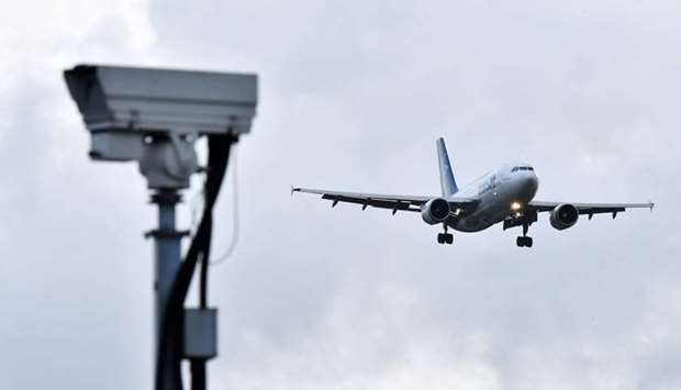 An Air Transat aircraft is pictured beyond a CCTV camera as it prepares to land at London Gatwick Ai