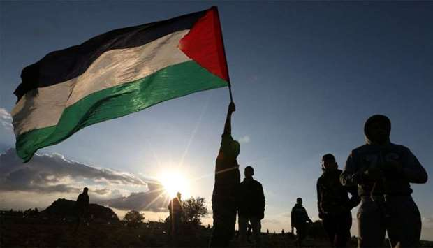 Demonstrator holds a Palestinian flag during a protest near the Israel-Gaza border fence, in the sou
