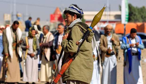 An armed Yemeni man holds a rocket launcher as people gather in the capital Sanaa